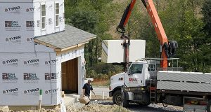 A crane lifts a load of drywall as construction is under way at a housing development in Zelienople, Pa. The National Association of Home Builders reports on sentiment among U.S. builders on Wednesday, Sept. 17, 2014. (AP Photo/Keith Srakocic)