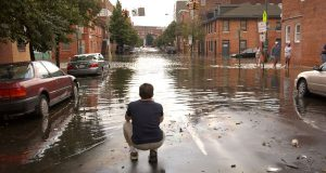 Flooding from Hurricane Isabel washes through the intersection of Aliceanna and South Wolfe streets in Fells Point in 2003. (The Daily Record/Maximilian Franz)