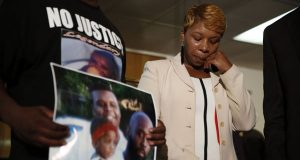 Lesley McSpadden, the mother of Michael Brown, wipes away tears as Brown's father, Michael Brown Sr., holds up a family picture of himself, his son, top left, and a young child during a news conference in Jennings, Mo. (AP Photo/Jeff Roberson, File)