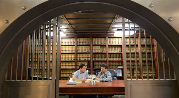From left, Kristofer P. Cubello, of the Law Office of Marc Seldin Rosen, works with Dan Miller in the former vault of the Baltimore Commercial Bank, which is now the conference room of their shared office space. Miller purchased the building in May. (Daily Record/Maximilian Franz)