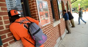 An Orioles fan buys tickets ahead of the Tuesday's game against the Toronto Blue Jays. If the team wins it would be the first time it won the American League East at home since 1979. (The Daily Record/Maximilian Franz)