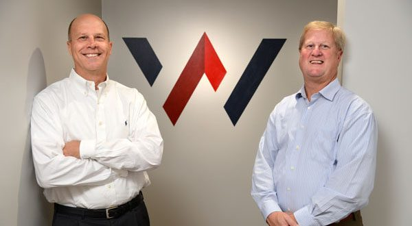 From left, Joseph N. Geier, Winpoint president and CEO, with Brian Woods, vice president, in front of their new company logo. (The Daily Record/Maximilian Franz)