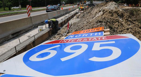 Construction workers build new medians around the bridge at Liberty Road and Interstate 695. Both gubernatorial candidates are pledging state funds for local road projects, but they differ on other transportation issues. (The Daily Record/Maximilian Franz)