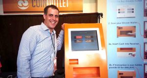 Eric Grill, CEO of CoinOutlet Inc., poses here with one of the company's bitcoin ATMs.