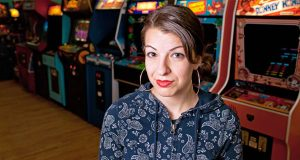 Anita Sarkeesian, shown with vintage video game machines in Minneapolis in January 2013, was not satisfied with the security arrangements at Utah State University. (AP Photo/Alex Lazara)