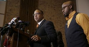 Anthony Gray, attorney for the family of Michael Brown, speaks as National Action Network Ferguson chapter president Rev. Carlton Lee, right, listens during a news conference in St. Louis County, Mo.(AP Photo/Jeff Roberson)