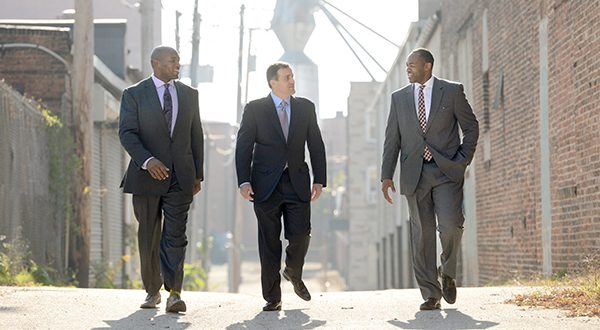 From left to right, Eugene Monroe, of 4th Down Partners, Arsh Mirmiran, of Caves Valley Partners, and 4th Down's Keith Payne Jr. Tuesday walk down Creek Alley in the Leadenhall community in South Baltimore where they plan to develop the Stadium Square mixed-use community. (The Daily Record/Maximilian Franz)