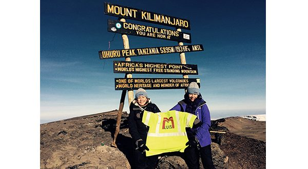 Shown here at the summit of Mt. Kilimanjaro in Tanzania, Cidalia Luis-Akbar (left) and Natalia Luis, co-owners of M. Luis Construction, hold up a reflective vest from their company. (Submitted photo)