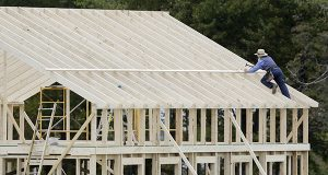 A man works on the roof of a building under construction in Middlefield, Ohio. The Commerce Department reports on U.S. construction spending in October on Tuesday, Dec. 2, 2014. (AP Photo/Tony Dejak, File)