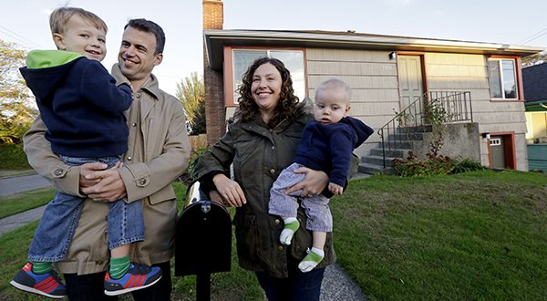 In this photo taken Wednesday, Oct. 15, 2014, Jennifer Ewing, second right, and her husband Florian Thiel pose for photos with their children Max, left, 3, and Felix, 8-months, outside their new home in Seattle's Ballard neighborhood. The couple recently closed on the three-bedroom house , which cost slightly less than $500,000. They moved to Seattle from New York, another city that matches the pattern of high-income jobs and even more expensive housing. (AP Photo/Elaine Thompson)
