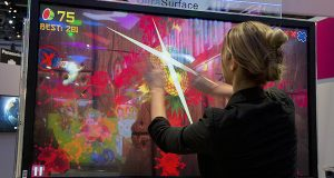 An attendee plays Fruit Ninja at the Panasonic booth at the Consumer Electronics Show in Las Vegas. More than a year after federal regulators issued new privacy rules for kids' mobile apps, online stores remain flooded with cute and silly software programs that quietly collect vast amounts of data on the youngest consumers, including a person's location and even recordings of their voice, according to privacy researchers and consumer advocates. (AP Photo/Julie Jacobson, File)