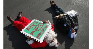 Freddie Chavez 'dies-in' as Santa Claus beside Marcus Macon as the men join a small group of protesters at the corner of Broadway and Market Street on Friday, Dec. 12, 2014. Protesters presented a holiday satire, marching against police brutality in downtown St. Louis.(AP Photo/St. Louis Post-Dispatch, Robert Cohen)
