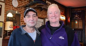 Dan Macatee, right, owner of Hull Street Blues Café, is joined by regular patron Paulie Santi. 'Back in the day when we first started, damn near every corner had its own spot,' Macatee says. (Capital News Service)
