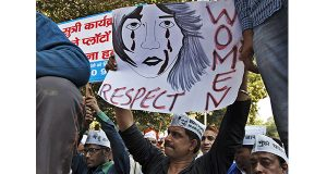 "In this Dec. 8, 2014 file photo, supporters of Aam Aadmi (Common Man) Party (AAP) hold placards during a protest after a woman was allegedly raped by a driver from ride-booking service Uber in New Delhi, India. Uber promises to focus on rider safety amid increasing concerns that its drivers are not adequately screened for past criminal convictions. In a blog post Wednesday, Dec. 17, 2014, Uber's head of global safety defended the company's safety record but also wrote that ""as we look to 2015, we will build new safety programs and intensify others."" (AP Photo/Tsering Topgyal, File)"