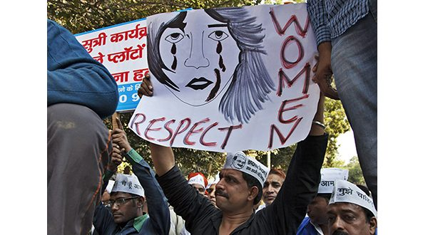 """In this Dec. 8, 2014 file photo, supporters of Aam Aadmi (Common Man) Party (AAP) hold placards during a protest after a woman was allegedly raped by a driver from ride-booking service Uber in New Delhi, India. Uber promises to focus on rider safety amid increasing concerns that its drivers are not adequately screened for past criminal convictions. In a blog post Wednesday, Dec. 17, 2014, Uber's head of global safety defended the company's safety record but also wrote that """"as we look to 2015, we will build new safety programs and intensify others."""" (AP Photo/Tsering Topgyal, File)"""