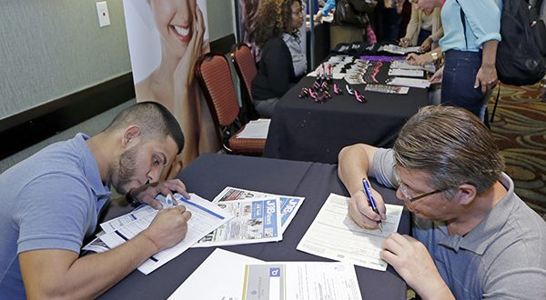Job seekers Stevens de la Pena, foreground left, and Eduardo Perez, foreground right, fill out a job application at a job fair in Miami Lakes, Fla. The Labor Department releases weekly jobless claims on Wednesday, Nov. 26, 2014. (AP Photo/Alan Diaz)