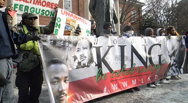 A man who identified himself as Shaka Zulu (in neon-green vest) stands with protesters near the State House on Thursday to demand justice for victims of police violence [Capital News Service photo, Nate Rabner]