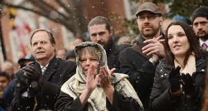 Snow falls on people clapping in the crowd at the Hogan inauguration in 2015. (The Daily Record/Maximilian Franz)
