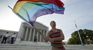 In this June 26, 2013, file photo, gay rights advocate Vin Testa waves a rainbow flag in front of the Supreme Court in Washington. The justices might have to decide to jump in at their closed-door conference on Friday, Jan. 16, 2015, if they want to resolve the legal debate over gay marriage in the next few months. The justices would hear the case in April, the last month for oral arguments before the next term begins in October. (AP Photo/J. Scott Applewhite, File)