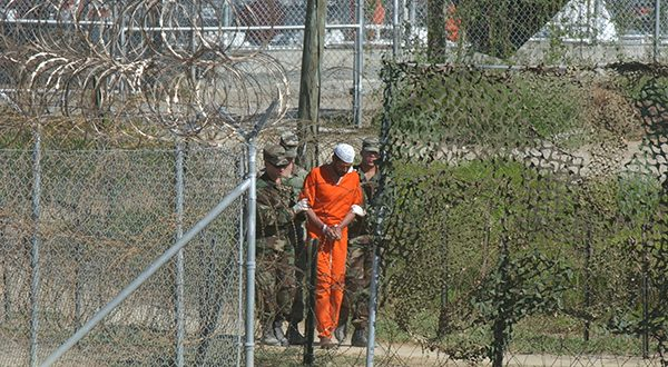 A detainee is escorted to interrogation by U.S. military guards at Camp X-Ray at Guantanamo Bay U.S. Naval Base, Cuba, in March 2002. (AP Photo/file)