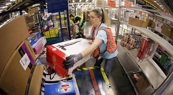 Teresa Clark fills an order at the Amazon fulfillment center in Lebanon, Tennessee. Shares of Amazon.com jumped over 8 percent in aftermarket trading after the e-commerce giant beat quarterly profit expectations by a mile. (AP Photo/Mark Humphrey)