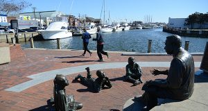 Joggers run past a sculpture at City Dock in Annapolis. Development plans for the area have been stymied amid concerns that the city's historic ambiance would be damaged. (The Daily Record/Maximilian Franz)