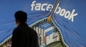 In this June 11, 2014 file photo, a man walks past a mural in an office on the Facebook campus in Menlo Park, Calif. (AP Photo/Jeff Chiu, File)
