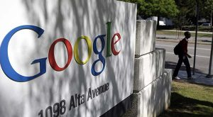 FILE - In this June 5, 2014 file photo, a man walks past a Google sign at the company's headquarters in Mountain View, Calif. The Justice Department is at odds with Google and privacy groups over the government's push to make it easier to locate and hack into computers in criminal investigations.  (AP Photo/Marcio Jose Sanchez, File)