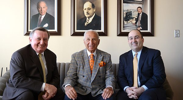 From left, Howard L. Alderman, Jr., Stanford G. Gann, Sr., and Stanford G. Gann, Jr., attorneys at Levin & Gann P.A., sit in the boardroom under some photos of their firm's founding members. (The Daily Record/Maximilian Franz)