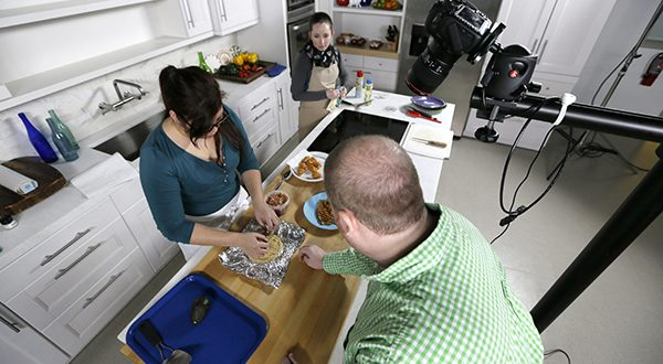 Workers in a kitchen studio produce a video about fish tacos at Meredith Corp. headquarters in Des Moines, Iowa. Meredith has survived depression, recession, the Internet and an increasingly crowded field of magazine competitors to become the nation's top publisher focused on women, reaching more than 200 million people a month. (AP PHOTO/CHARLIE NEIBERGALL)