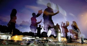 Protesters march in the street as lightning flashes in the distance in Ferguson, Mo., last August, days after police officer Darren Wilson fatally shot 18-year-old Michael Brown. (AP Photo)