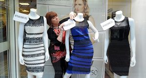 Shop manager Debbie Armstrong adjusts a two-tone Roman Originals dress in a window display at a Roman Originals shop in Lichfield, England. Over the course of a few days, the debate over whether the dress was blue and black or white and gold stirred social networks and led to a frenzy. Sales of the frock are up 600 percent since the end of February. (AP PHOTO/RUI VIEIRA, FILE)