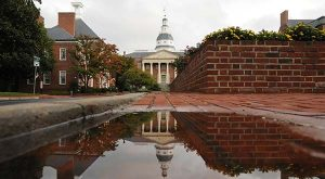 The Maryland State House is shown here in a reflection pool along Rowe Boulevard in Annapolis on a rainy day.  (Maximilian Franz/The Daily Record)