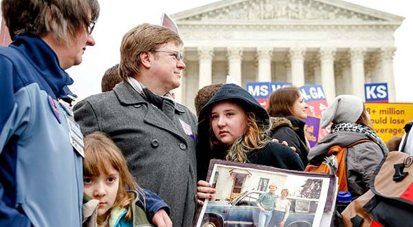 Michelle Boyle, left, and Ray Roberts, third from left, of Pittsburgh, stand with their daughters Cassie Boyle, second from left, and Helena Roberts, 11, center, during a rally outside the Supreme Court in Washington on Wednesday. The Supreme Court was hearing arguments in King v. Burwell, a major test of President Barack Obama's health overhaul which, if successful, could halt health care premium subsidies in all the states where the federal government runs the insurance marketplaces. Cassie holds a photograph of Ray's mother, Hanna Brown, who died of complications due to Parkinson's disease in 1998 when she lost her health care coverage when she lost her job. (AP Photo/Andrew Harnik)