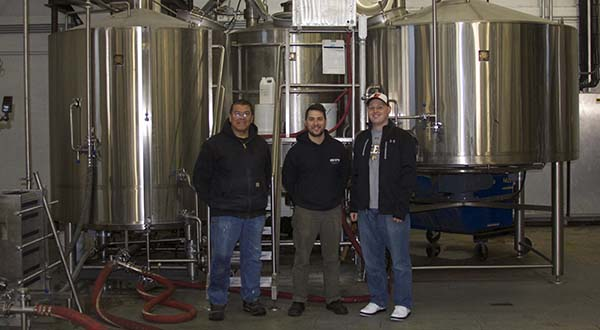 From left, Peabody Heights brewmaster Ernie L. Igot, brewer Eli Breitburg-Smith and co-owner Dan Baumiller stand in front of the machine responsible for distilling beer flavors before the beer enters its fermentation stage. (Capital News Service photo by Katelyn Newman)
