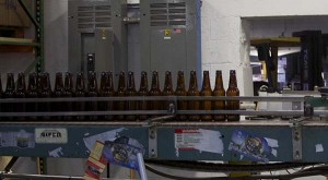 Empty bottles wait on a conveyor belt to be labeled, filled and packaged for sale. Full Tilt's Bay IPA stickers hang off the machine's side. (Capital News Service photo by Katelyn Newman)
