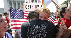 In this photo taken June 26, 2013, Michael Knaapen, left, and his husband John Becker, right, embrace outside the Supreme Court in Washington after the court struck down a federal provision denying benefits to legally married gay couples. (AP Photo/Charles Dharapak)