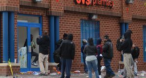 Looters making off with the last bit of merchendice from the CVS at the corner of Pennsylvainnia and North Avenue on Monday evening around 6:30pm.(The Daily Record/Maximilian Franz)
