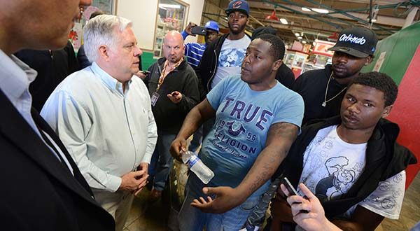 Governor Larry Hogan speaking with 22 year old Harry Collic and a group of his friends at the Avenue market on Pennsylvania Avenue while touring neighborhoods in a call for peace this weekend. (The Daily Record/Maximilian Franz).