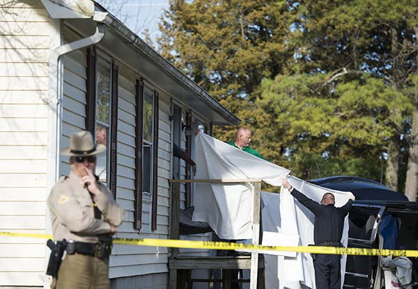 Sheets are held as a body is removed from a residence where seven children and one adult were found dead Monday in Princess Anne. Officers were sent to the home Monday after being contacted by a concerned co-worker of the adult. (AP Photo/The Daily Times, Joe Lamberti)