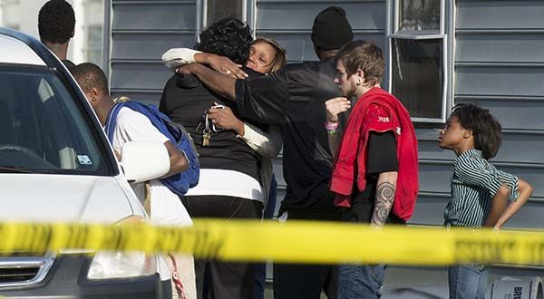Onlookers gather outside of a house, where police say seven children and one adult have been found dead Monday in Princess Anne. Police were sent to the home Monday after being contacted by a concerned co-worker of the adult. (AP Photo/The Daily Times, Joe Lamberti)