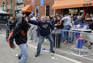A protestor, left, fights with a bar patron outside of a bar near Oriole Park at Camden Yards on Saturday after a rally for Freddie Gray. (AP Photo/Patrick Semansky)