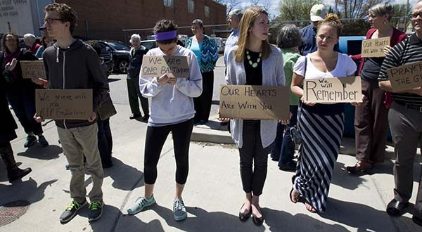 From left, David Pontious, Moira Pannepacker, Kelly Lussier and Juliana Restrivo, hold support signs for Freddie Gray outside of Vaughn Greene Funeral Home, during his wake Sunday, April 26, 2015 in Baltimore. Gray died from spinal injuries about a week after he was arrested and transported in a police van. (AP Photo/Jose Luis Magana)
