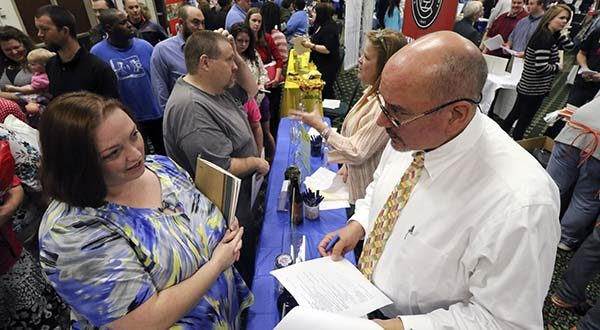Frances Scoggins, left, speaks to Michael McCall, general manager for Chattanooga Labeling Systems, about her resume during a huge 15-county North Georgia job fair at The Colonnade in Ringgold, Ga., on Thursday, April 2, 2015. Scoggins has been unemployed for the past 4-months and is looking for a safety or manufacturing job. The U.S. government issued the March jobs report on Friday. (AP Photo/Chattanooga Times Free Press, Dan Henry)