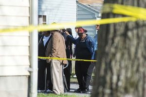 Onlookers gather outside of a house, where police say seven children and one adult were found dead Monday. (AP Photo/The Daily Times, Joe Lamberti)