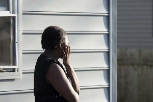 A woman looks away as bodies are removed from a house, where seven children and one adult were found dead Monday. (AP Photo/The Daily Times, Joe Lamberti)
