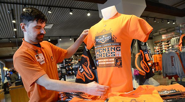 Johnathan Moore, retail supervisor, adjusts the display of 2015 Opening Series shirts in the Orioles Team Store at Oriole Park at Camden Yards. (The Daily Record/Maximilian Franz)