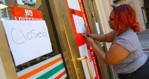 Matrice Davis, 711 worker at the corner of Charles and Saratoga, placing closed signs on the front entrance that was busted open Monday during the looting. (The Daily Record/Maximilian Franz)