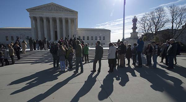 In this photo taken March 23, 2015, people wait outside the Supreme Court in Washington in hopes to gain admittance for oral arguments. Protesters who demonstrated inside the U.S. Supreme Court are facing the threat of a year in jail and stiff fines, a sign that prosecutors and the justices themselves are losing patience over the courtroom interruptions after the third protest in just over a year. Five people arrested last week after voicing displeasure with court decisions that removed limits on political campaign contributions now face charges including one that carries a maximum jail term of a year and up to a $100,000 fine _ a sharp escalation from the possible penalties sought after two earlier protests. (AP Photo/Molly Riley)