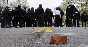 A brick sits on a street as unidentified police stand by on April 27, 2015, during a skirmish after the funeral of Freddie Gray in Baltimore. (AP Photo/Patrick Semansky)